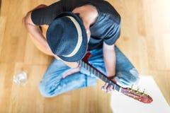 Young asian man playing spanish guitar indoors stock images
