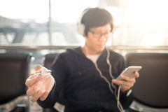 Young asian man playing spinner fidget in airport. Young asian man playing spinner fidget while waiting for the airplane flight in airport terminal, using smart stock photography