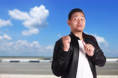 Young Asian Man Pointing Something Behind Him. Portrait of attractive young Asian man wearing black leather jacket smiling and pointing something behind him stock images