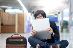 Young asian man with laptop on trolley in airport terminal. Young asian man posing with laptop computer on airport trolley during waiting for a connecting flight Stock Image