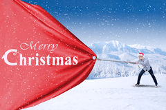 Young asian man is pulling christmas banner Stock Image