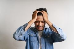 Free Young Asian Man Put Hands To His Head. He Feeling Sick And Headache Due To Having Some Problems. His Stress Make Him Uncomfortable Royalty Free Stock Photography - 145454757
