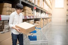 Young Asian man putting paper box into trolley cart in warehouse royalty free stock photos