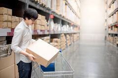 Young Asian man putting paper box into trolley cart in warehouse. Shopping warehousing concept Stock Photos