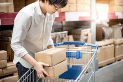 Young Asian man putting paper boxes into trolley cart in warehou. Se, shopping warehousing concept Stock Photos