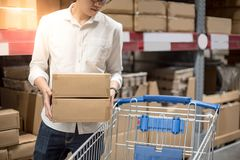 Young Asian man putting paper boxes into trolley cart in warehou. Se, shopping warehousing concept Royalty Free Stock Image