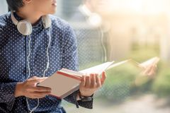 Young Asian man reading book in library. Young Asian man half face reading book in library with reflection on mirror. high school or university college student Stock Images