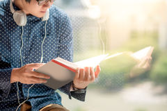 Young Asian man reading book in library. Young Asian man half face reading book in library with reflection on mirror. high school or university college student Royalty Free Stock Photos