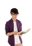 Young Asian man reading book. A young Asian man standing in a checkered shirt and glasses, holding Stock Images
