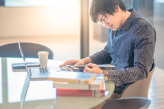Young Asian man reading book in workspace Stock Images