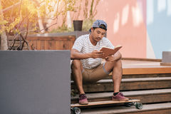 Young Asian man relaxing on stairs outside reading a book. Casually dressed young Asian man in a cap reading a novel while sitting alone on some stairs with his Stock Image