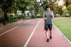 Young Asian man runner jogging on running track in the park. Young Asian man runner with sport clothes and smart watch jogging on red running track in the park Royalty Free Stock Images