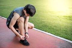 Young Asian man runner tying shoe laces on running trail. Young Asian man runner wearing sport clothes and smart watch tying shoe laces on running track. Healthy Stock Photo