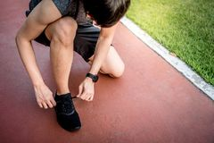 Young Asian man runner tying shoe laces on running trail. Young Asian man runner wearing sport clothes and smart watch tying shoe laces on running track. Healthy Royalty Free Stock Photos