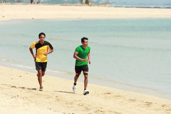 Young Asian man running on beach, Sport concept Stock Photos