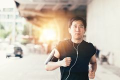 Young Asian man running in the city and wearing headphone. Young determined athletic Asian man wearing headphone and armband with smart phone inside. He is stock photo