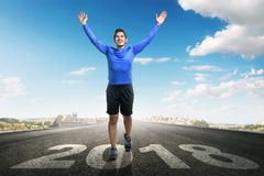Happy New Year 2018. Young asian man running with 2018 number on asphalt road. Happy New Year 2018 Stock Image