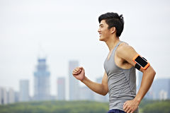 Young asian man running in park stock photos
