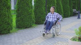 Young asian man disabled in wheelchair rides in park stock video footage