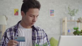 Young asian man in a shirt enters data with a Bank card on a laptop close up. Young asian man in a shirt enters data with a Bank card on a laptop in living room stock footage