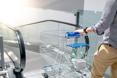 Asian man holding shopping cart on travelator. Young Asian man shopper holding shopping cart trolley on travelator escalator in supermarket or grocery store Royalty Free Stock Photography