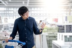 Young Asian man shopping with trolley cart in warehouse. Young Asian happy man using trolley cart choosing empty bottle. Shopping home improvement stuff in Stock Photography