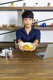 Young asian man showing breakfast with coffee and laptop on wooden table. In shelf background of kitchen room royalty free stock photo