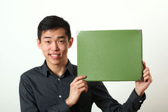 Young Asian man showing green copy space box Stock Photo