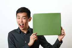 Young Asian man showing green copy space box Royalty Free Stock Photography