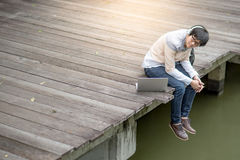 Young Asian man sitting on bridge listening to music. Young Asian man sitting on wooden bridge listening to music with headphones and laptop computer, male Stock Image