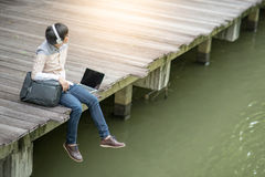 Young Asian man sitting on bridge listening to music. Young Asian man sitting on wooden bridge listening to music with headphones and laptop computer, male Stock Photography
