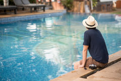 Young Asian man sitting on the edge of swimming pool. At resort, relaxing time and summer holiday vacation concepts Royalty Free Stock Photo