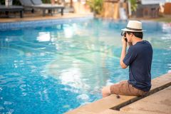 Young Asian man taking photo near of swimming pool. Young Asian man sitting on the edge of swimming pool and taking photo with his camera at resort, relaxing Royalty Free Stock Image