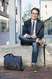 Young asian man sitting outside Stock Photo