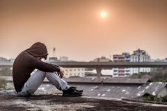 Young Asian man sitting rooftop of building with depression stre. Young Asian man sitting on rooftop of abandoned building with depression stress out during Royalty Free Stock Photos