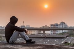 Young Asian man sitting rooftop of building with depression stre. Young Asian man sitting on rooftop of abandoned building with depression stress out during Stock Photo