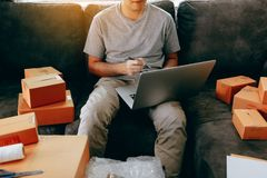 Young asian man sitting on sofa looking on computer laptop and writing order list on paper, SME concept royalty free stock photography