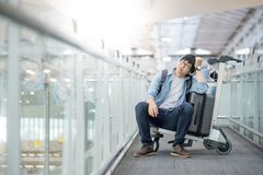 Young asian man sitting on trolley in airport terminal Stock Photography
