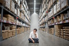 Young Asian man sitting in warehouse choosing what to buy Royalty Free Stock Photography