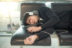 Young Asian man sleeping on bench in airport terminal. Young Asian man with eyeglasses and headphones sleeping on bench while waiting for connecting flight in royalty free stock image