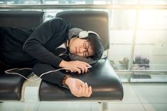 Young Asian man sleeping on bench in airport terminal. Young Asian man with eyeglasses and headphones sleeping on bench while waiting for connecting flight in royalty free stock photography