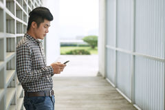 Young Asian man with smartphone Royalty Free Stock Photos