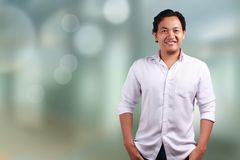 Man Smiling confidence. Young Asian Man Smiling confidence wearing a white shirt, looking at camera royalty free stock photos