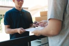 Young asian man smiling while delivering a cardboard box to the woman holding document to signing signature royalty free stock image