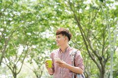 Young asian man smiling and using phone in park Stock Photo