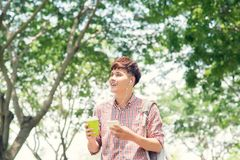 Young asian man smiling and using phone in park Royalty Free Stock Photos