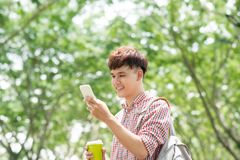 Young asian man smiling and using phone in park Stock Photos
