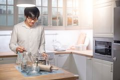 Young Asian man standing by counter in kitchen stock photos
