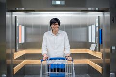 Young Asian man standing with trolley cart in lift or elevator. Young Asian man standing with empty trolley cart in lift or elevator. shopping in warehouse Royalty Free Stock Images