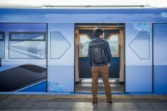 Young Asian man standing in front of the metro train. On station platform in the city. Urban lifestyle concept Stock Image